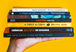 Mão segurando livros sob fundo amarelo